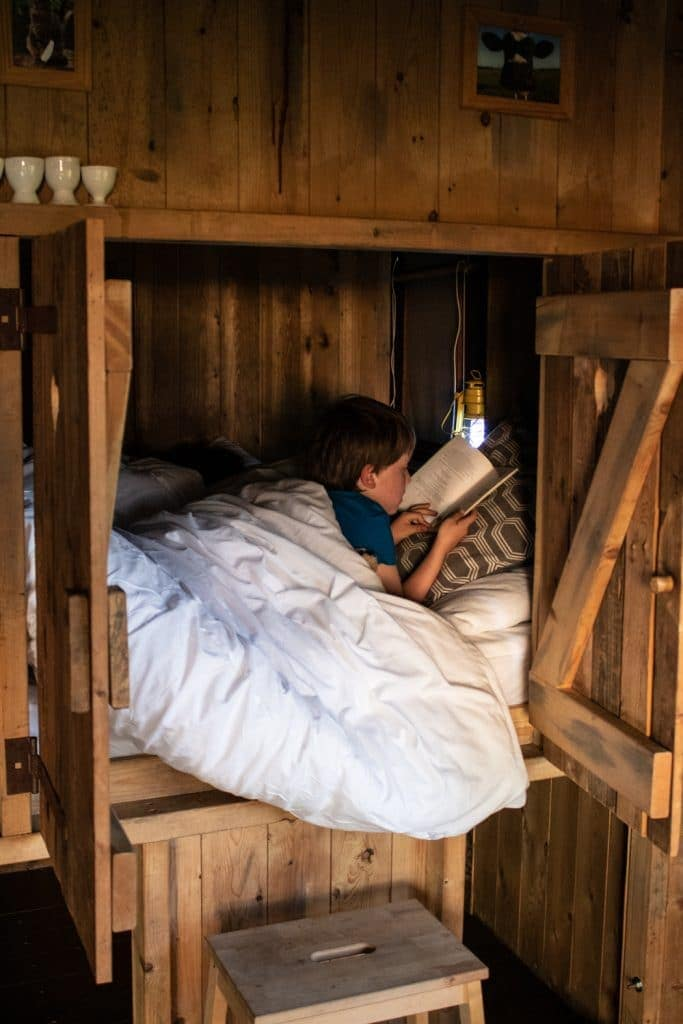 Child reading in the featherdown farms cupboard bed