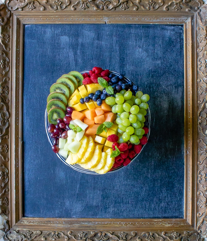 A fruit platter recipe on a cake stand surrounded by a vintage gilded picture frame.