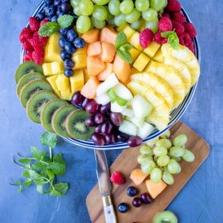 Fruit platter served on a cake stand surrounded by chopped fruit salad ingredients on a blue background.