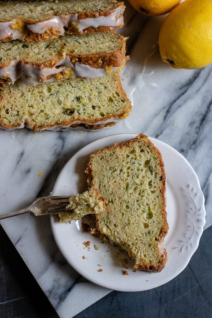 Slice of zucchini cake with lemon drizzle on a vintage white plate on a marble slab with lemons in the corner. Click for the recipe.