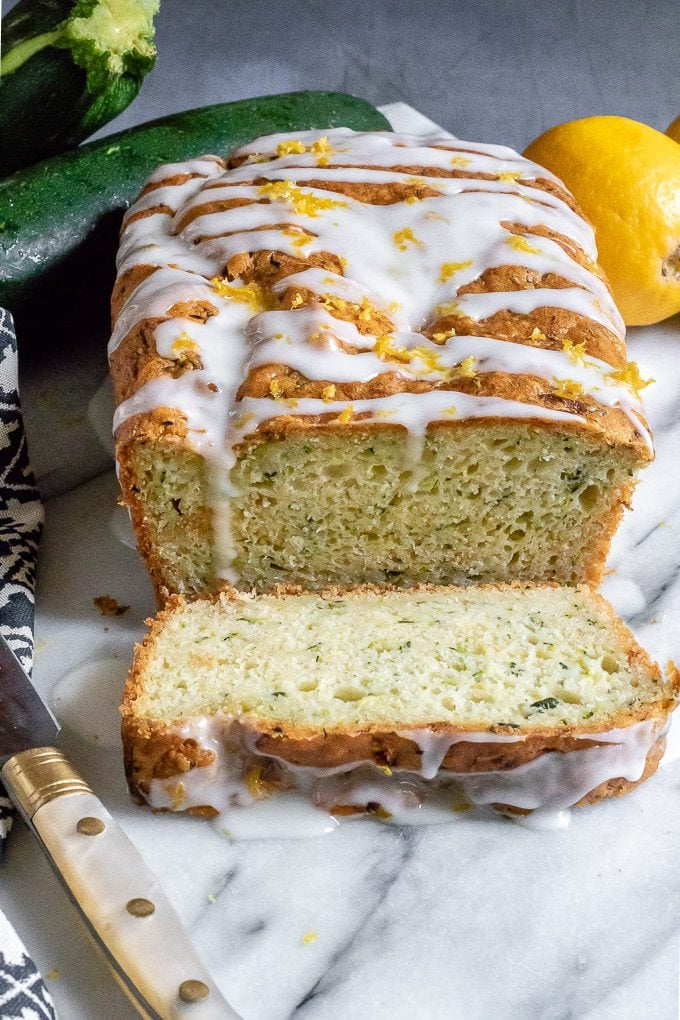 Close up of green flecked courgette cake with lemon drizzle sprinkled with lemon zest. Courgettes / zucchini and lemons in the background. Click for the courgette cake recipe.