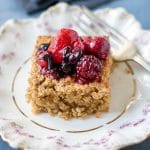 A slice of baked oatmeal topped with mixed berries on a vintage plate