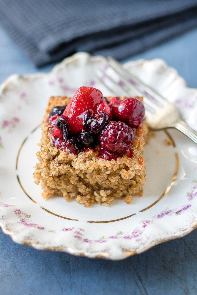 A slice of baked oatmeal topped with mixed berries on a vintage plate.