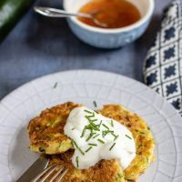 A plate with cheesy courgette fritters recipe topped with sour cream and chopped chives, next to a bowl of sweet chilli sauce.