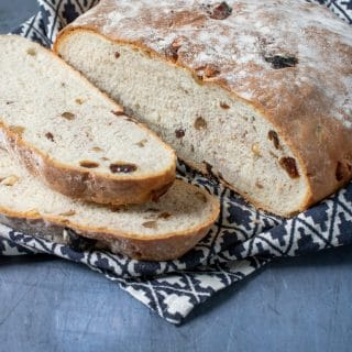A freshly baked date and walnut loaf on a blue background with patterned tea towel and two slices cut from the bread.