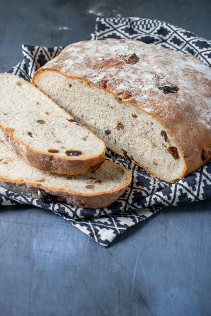 A freshly baked date and walnut bread on a blue background with patterned tea towel and two slices cut from the bread.
