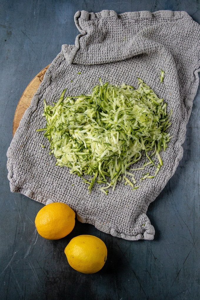 Grated courgette in a tea towel.