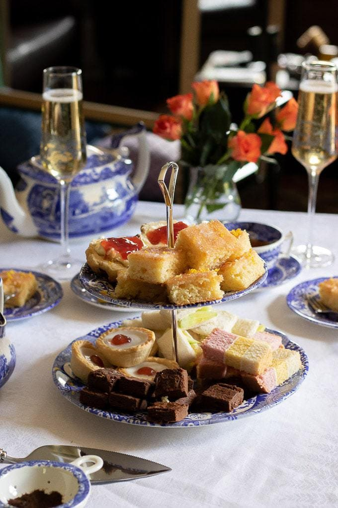 A table of afternoon tea, with full cake stand, including lemon drizzle traycake and scones, plus champagne and tea