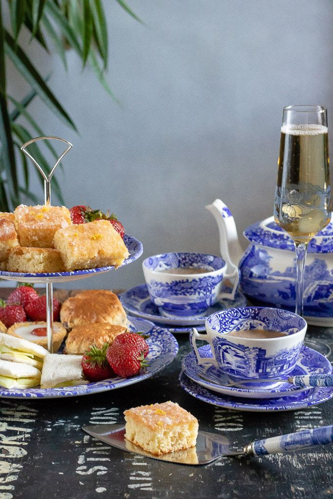 Afternoon tea, with a cake stand of cucumber sandwiches, scones and lemon drizzle squares, with blue and
