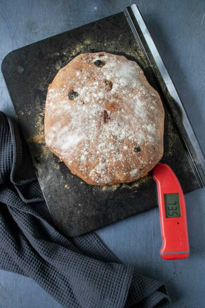 Using a Thermapen digital food thermometer to test a loaf of bread for doneness