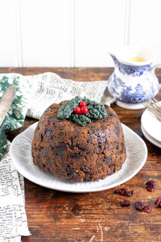 A traditional Christmas pudding, with hidden Cavolo Nero kale! This vegetarian Xmas pudding is on a plate next to a vintage jug of custard.