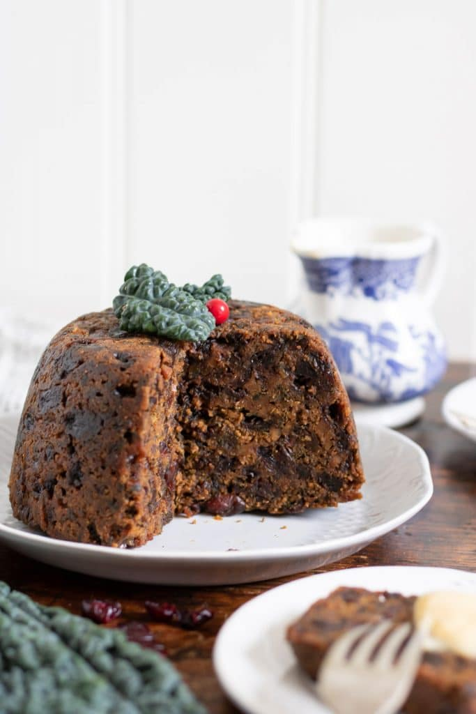 A traditional Xmas pudding, but with kale! This cavolo nero Christmas pudding looks traditional but has hidden veg. It's on a white plate next to a vintage jug full of custard.