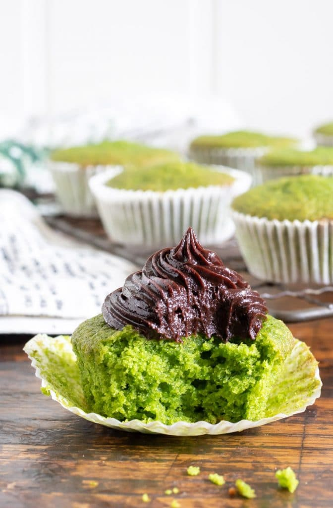 A bright green Cavolo Nero kale cupcake with a bite taken out, topped with chocolate frosting
