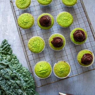 A dozen green cavolo nero cupcakes cooling on a vintage rack, with some being topped with chocolate frosting