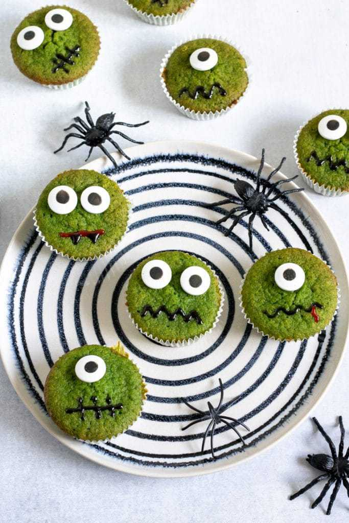 A plate of halloween cupcakes - a healthier halloween recipe because spinach makes the cupcakes naturally green. Decorated with candy eyes and writing icing mouths.