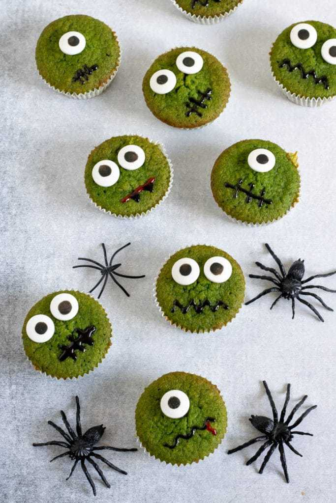 Lots of halloween cupcakes on a white background. These are vegetable cakes - the green colour is natural from spinach, but you can't taste it.