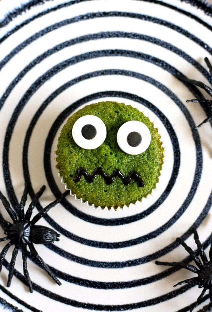A black and white plate with a bright green halloween cupcake decorated with candy eyes and icing mouth. The recipe is green because of hidden vegetable - spinach! But you can't taste it.