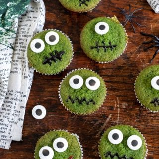 Wooden background with overhead shot of halloween cupcakes - this recipe makes naturally bright green cupcakes - with spinach. You can't taste it but they are a great hidden vegetable cake.