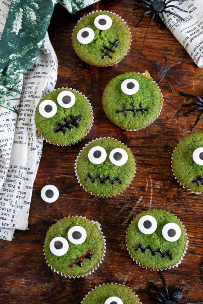 Cupcakes decorated with candy eyes on a wooden table.