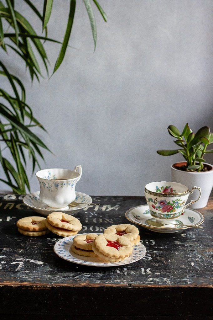 Tea cups and a vintage plate of jammy dodgers (recipe also known as linzer cookies), shortbread with jam in the middle and star cut out of the top biscuit.