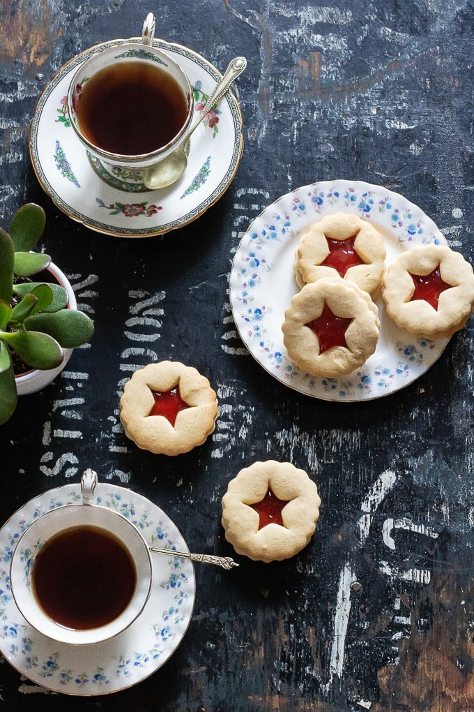 Jammie dodgers (recipe also called Linzer cookies) biscuits on vintage plates with teacups