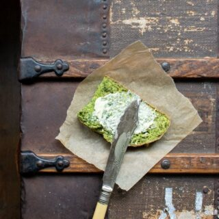 A slice of bright green kale herb soda bread with butter and vintage knife on antique trunk. An easy no-rise bread recipe