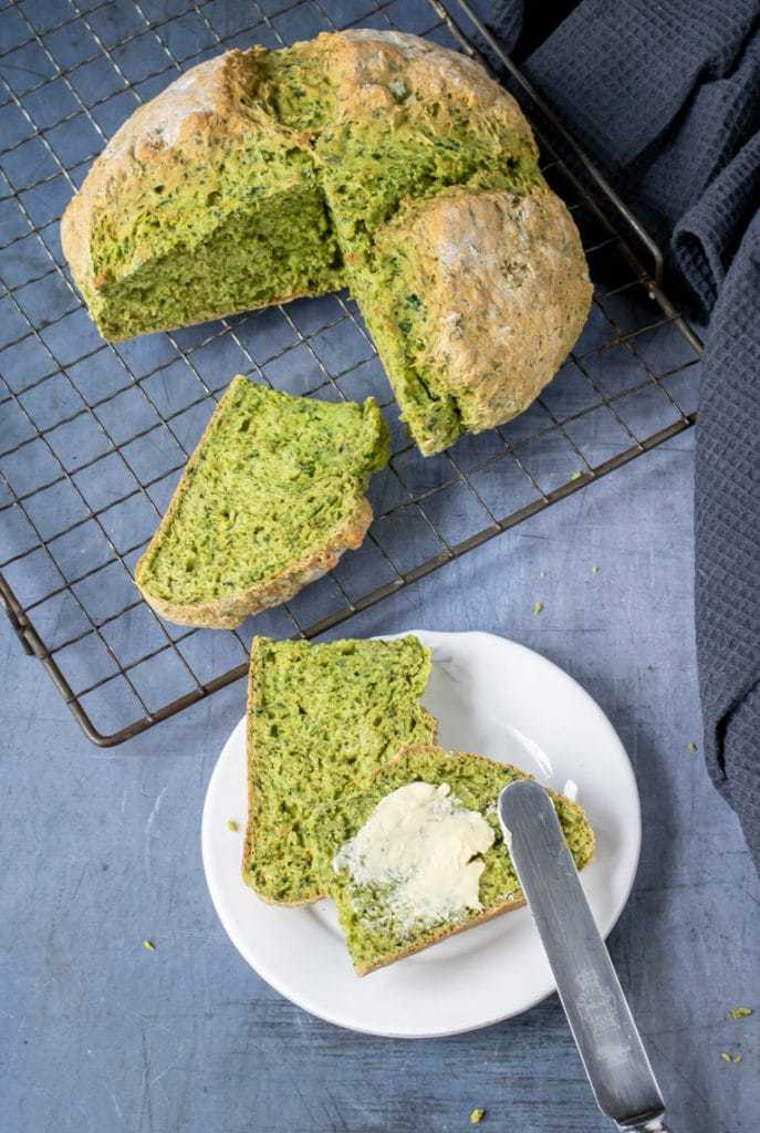 A loaf of kale herb soda bread, with slices cut out.