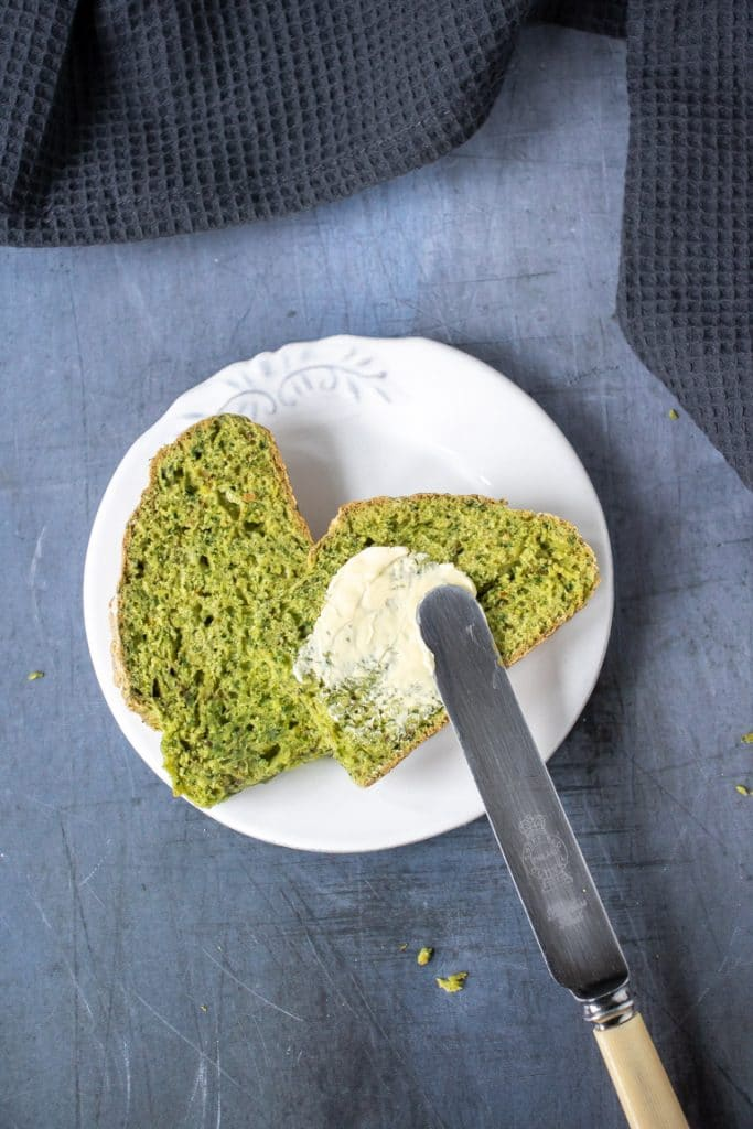 Slices of kale herb soda bread on a plate with vintage knife. Get the easy soda bread recipe now.