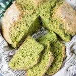 A loaf of kale herb soda bread recipe with slices cut out
