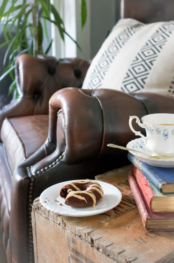 Vegan chocolate donut on a side table next to vintage books and teacup