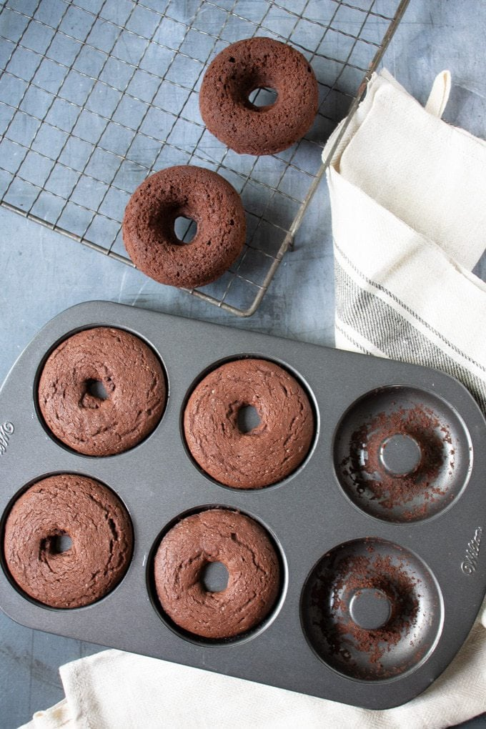 A tray of baked chocolate vegan donuts next to a vintage cooling rack.
