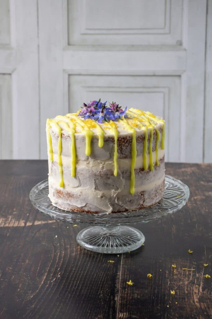 A fluffy vegan lemon layer cake in three layers with lemon icing and bright yellow lemon drip icing topped with edible flowers