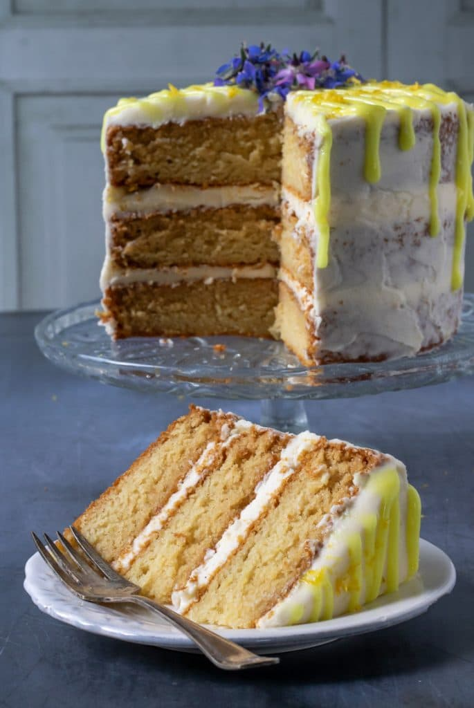 A vegan lemon layer cake that's light and fluffy with lemon icing and bright yellow lemon drizzle icing, with a slice cut out