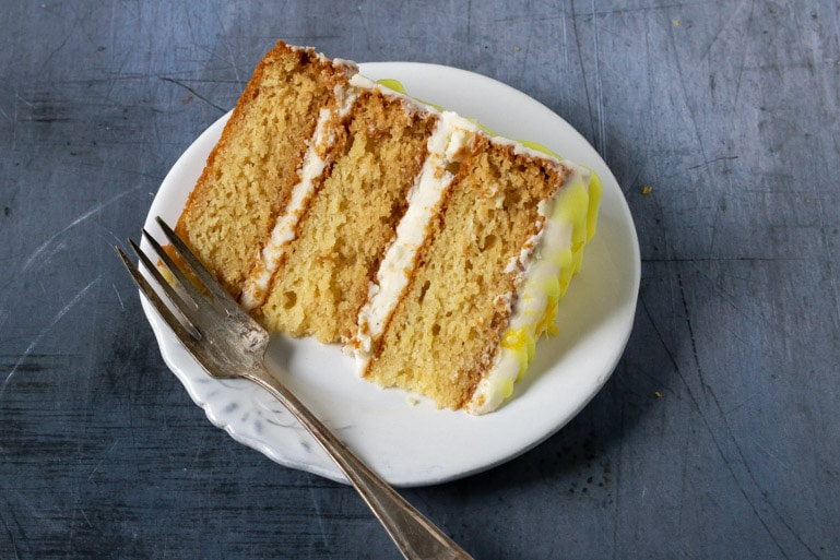 A plate with a slice of moist and fluffy three layer vegan lemon cake