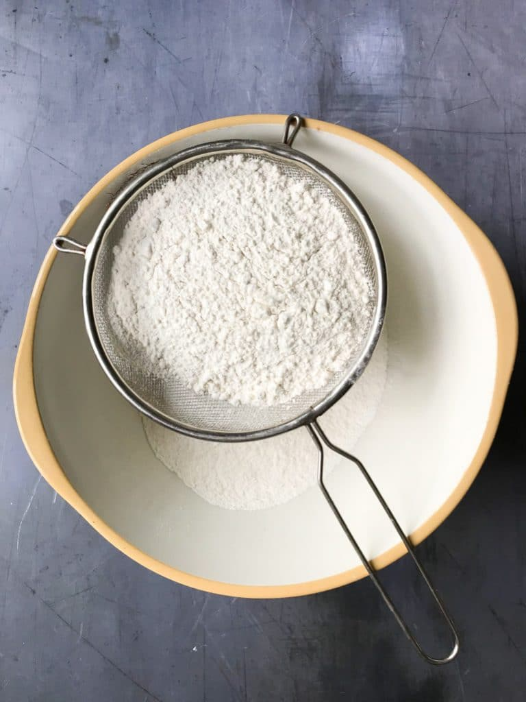 Flour in a sieve over a mixing bowl.