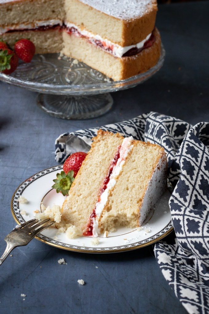 Fork taking a piece from a slice of light and fluffy vegan Victoria sandwich cake. The recipe is tasty and filled with vegan buttercream and strawberry jam.