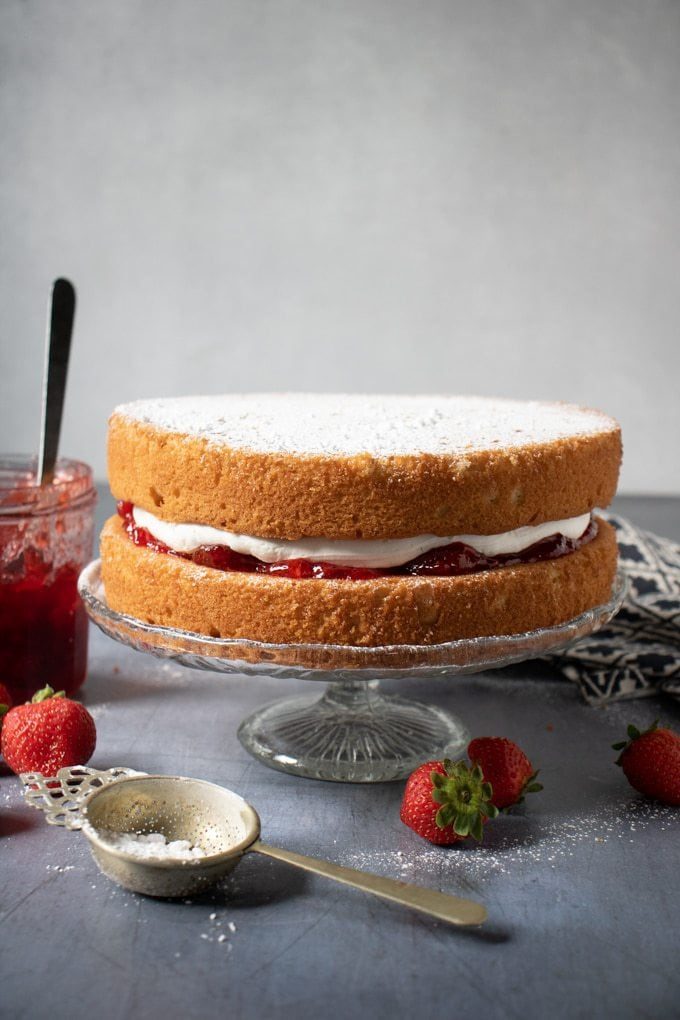 Vegan Victoria sponge cake on a cake stand with strawberry jam next to it. Get the recipe.