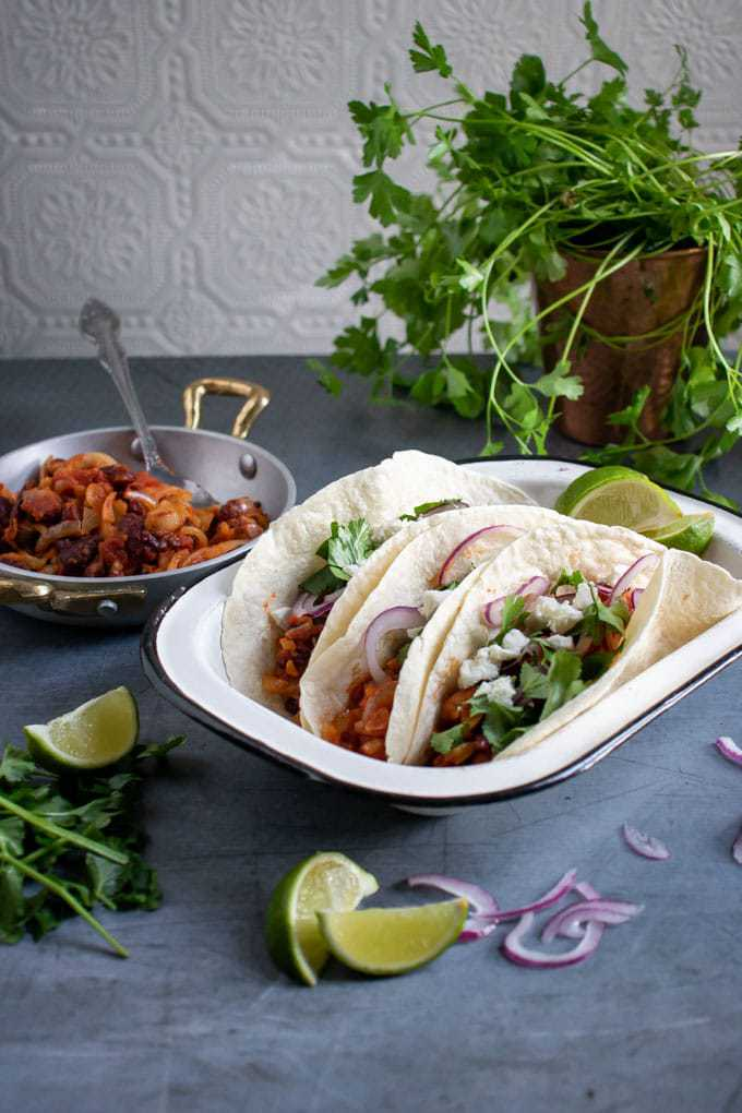 Enamel dish with three vegetarian tacos - made in a Tefal Actifry air fryer. In front of fresh coriander, limes and red onion.