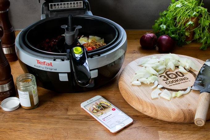 Tefal Actifry Original air fryer, next to a chopping board with onions.