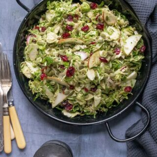 A black dish of shredded raw sprout salad, with apples, red onion, dried cranberries and a delicious easy toasted pumpkin seed dressing. An easy recipe, shown on a dark background with grey napkin and vintage salt and pepper mills.