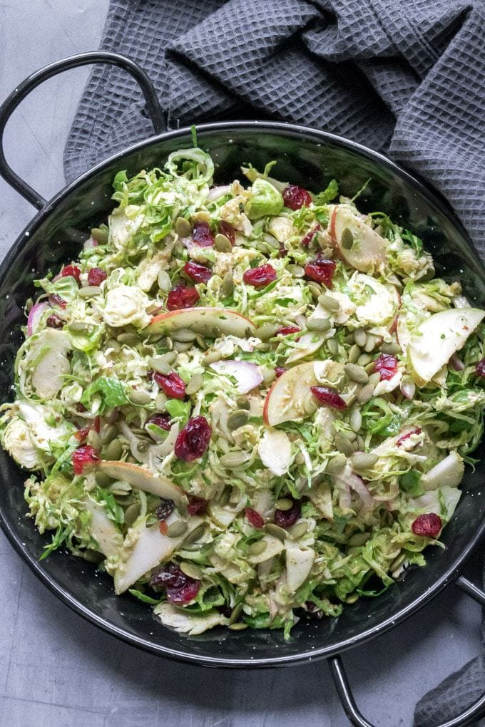 Close up of a raw Brussels sprout salad, with apples, red onion, dried cranberries and a delicious easy pumpkin seed dressing. A perfect winter salad recipe. Shown on a black serving dish on a dark napkin.