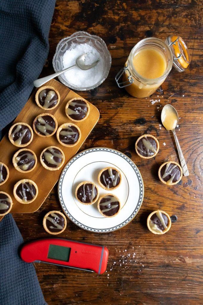 Wooden table with chocolate tarts, jar of salted caramel sauce, sea salt. Get the recipe.