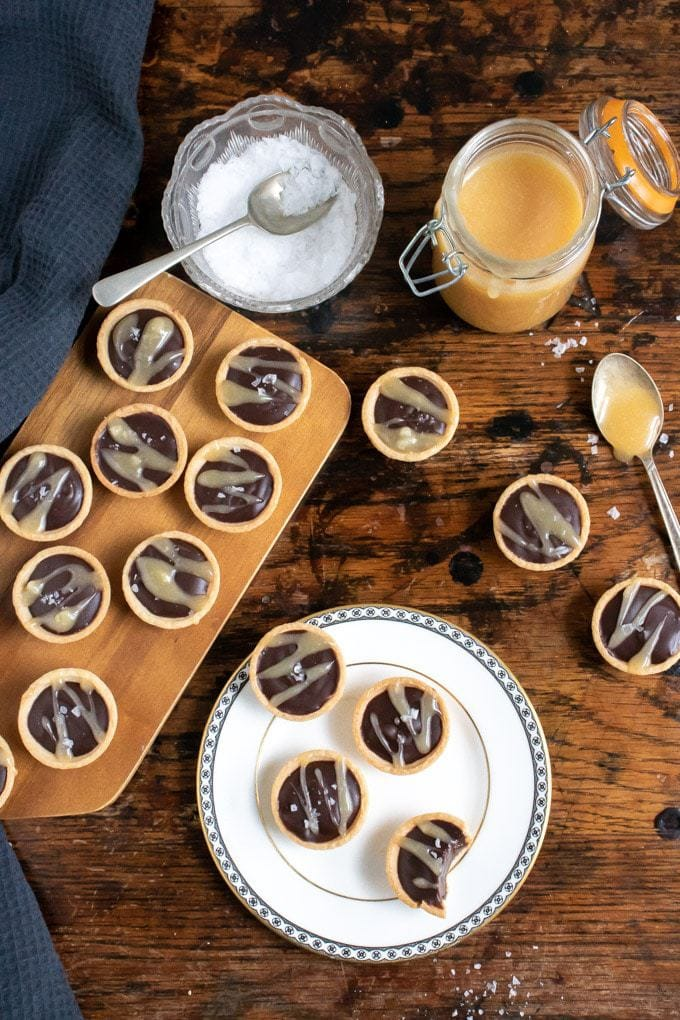Mini chocolate tarts with salted caramel sauce, shown on a wooden tray and a white vintage plate next to a dish of salt and jar of caramel.