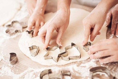 Kids and adult cutting out cookies with cutters