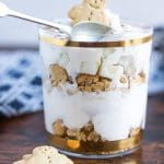 A glass of no bake layered dessert: Pear Gingerbread Parfaits - layers of crushed gingerbread men, gingerbread spiced yogurt and chopped pear.
