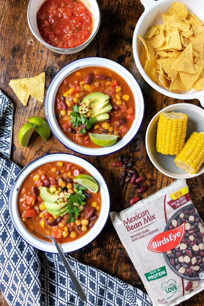 Bowls full of Mexican bean soup - a quick and easy recipe. Shown topped with avocado slices, wedge of lime, cilantro/coriander sprigs and a sprinkling of dried chilli flakes. Bowls of salsa, corn on the cob and tortilla chips on the side. Shown with Birds Eye Bean Mix packaging.