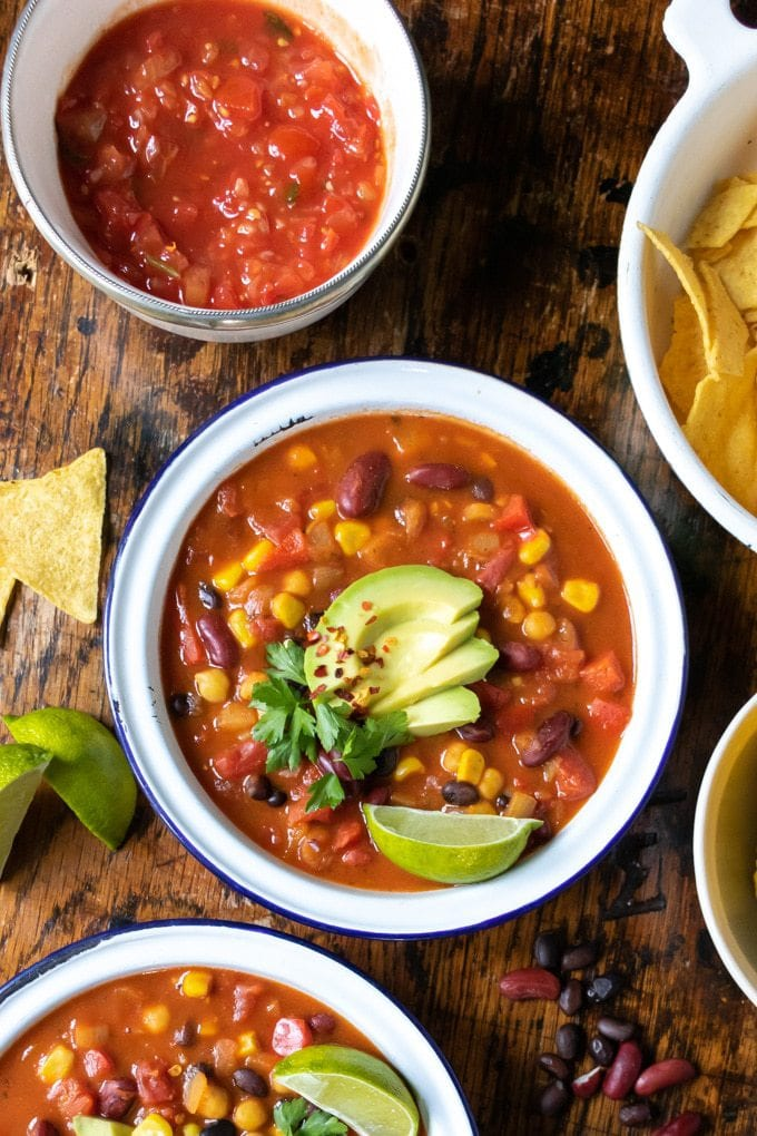 Bowls full of Mexican bean soup - a quick and easy recipe. Shown topped with avocado slices, wedge of lime, cilantro/coriander sprigs and a sprinkling of dried chilli flakes. With salsa, corn and tortillas on the side.