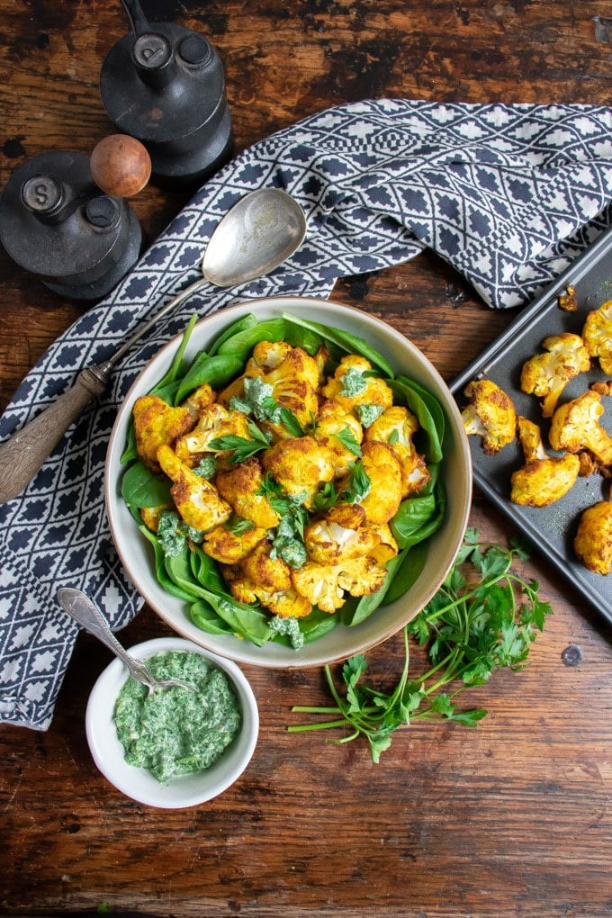 Table with bowl of spinach and roasted cauliflower.