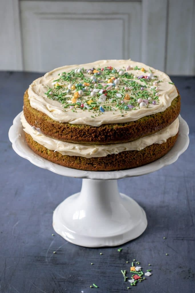 Vanilla Spinach Layer Cake with vanilla icing on a white cake stand on a blue background. The cake recipe is covered in pretty sprinkles.