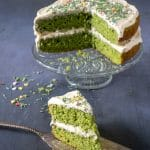A bright green vanilla spinach cake with vanilla frosting with a slice cut out and set in the foreground on a vintage cake server. The spinach flavour fades away in this fun layer cake recipe but leaves the cake bright green.